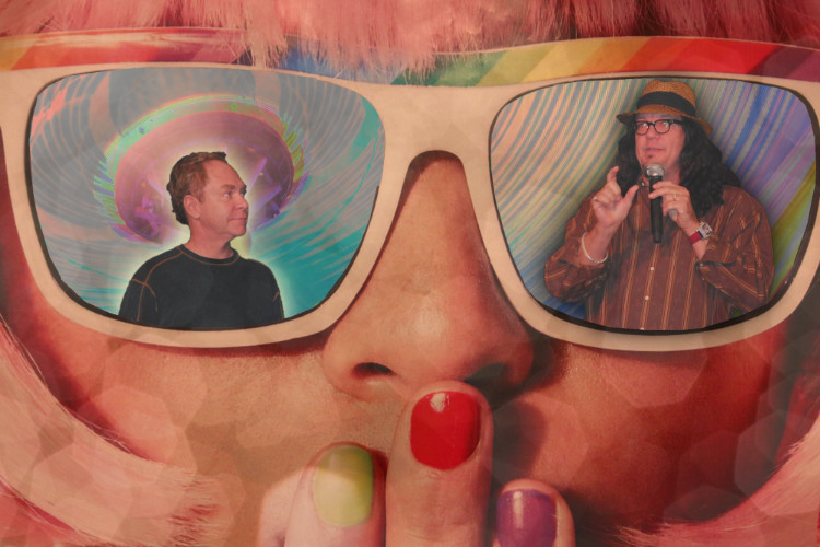 a photo of illustration of Penn and Teller, each in the individual lens of a pair of sunglasses; Penn looks at Teller, the colors are bright